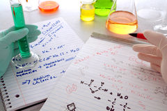 Chemistry Experiment in Science Research Lab. Scientist holding a pen over chemistry formulas on hand written notepads for assay notes comparison with a Stock Photography