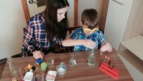 Chemistry experiments at home. Boy pours water from the bottle into the test tube using a pipette. Chemistry experiments at home. Boy pours water from the stock video