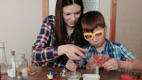 Chemistry experiments at home. Mom and son make a chemical reaction with the release of gas in the test tube. Chemistry experiments at home. Mom and son make a stock footage