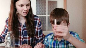Chemistry experiments at home. Woman puts the red paint in a test tube with water in the hands of the boy. Chemistry experiments at home. Woman puts the red stock video