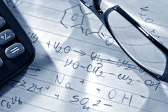 Chemistry Formulas in Science Research Lab. Chemistry formulas on hand written scientist notes with glasses and calculator in a science research lab Stock Photography