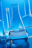 Chemistry glassware on blue background Royalty Free Stock Photo