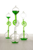 Chemistry glassware on the grey wooden table isolated. Chemistry science and experiment with green liquid thermometer Royalty Free Stock Images