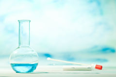Chemistry lab. Flask with blue liquid and sample stick in the background Royalty Free Stock Photography
