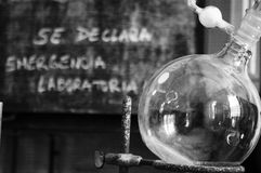 Chemistry Lab. A boiling flask with a blackboard in the background with a notice saying in spanish, Se declara emergencia laboratoria, which translates to Royalty Free Stock Photography