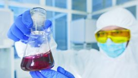 Chemistry lab - scientist in protective suit analyzing a liquid in laboratory flask. Chemistry lab - scientist in protective suit analyzing red liquid in stock video footage