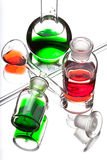 Chemistry laboratory glassware with colour liquids on white back Stock Photography