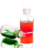 Chemistry laboratory glassware with colour liquids on white back Royalty Free Stock Photos