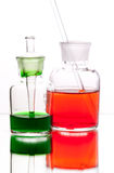 Chemistry laboratory glassware with colour liquids on white back Royalty Free Stock Images