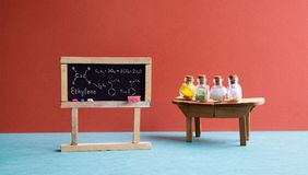 Chemistry lesson classroom laboratory. Black chalkboard with molecular formula ethylene, wooden table and chemical Royalty Free Stock Photo