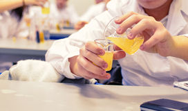 Chemistry lessons. Boy pouring liquids in glass recipients Stock Photo