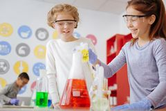 Cheerful teenage girls pouring chemical in flask during class. Chemistry lovers. Upbeat teenage female students pouring chemical into the flask and smiling while Stock Photography