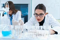 Young female researchers conducting laboratory test. Chemistry and medicine students working in a laboratory. Young female researchers doing lab tests stock images