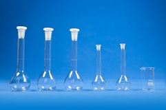 Chemistry science - flasks on blue background Royalty Free Stock Photos