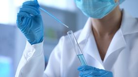 Chemistry scientist pouring blue liquid in lab tube, new detergents development stock photos