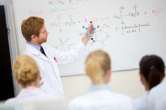 Chemistry teacher hold molecular model and teach students in cla. Young male chemistry teacher show molecular model to students in classroom Royalty Free Stock Image