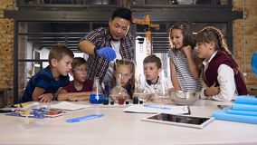 Chemistry teacher teaches young students to do chemical reaction experiments in lab class. Chemical reaction blue and orange color in glasses flask. Science stock footage