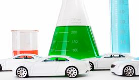 Chemistry and Transportation. Several brightly lit toy cars lined up in front of a glass Erlenmeyer flask with green colored liquid inside, small beaker stock photography