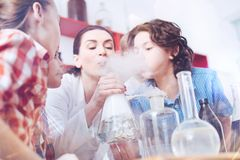 Chemistry tutor and elementary students blowing on fume in lab. Working together. Group of young scientists standing next to their teacher of chemistry blowing Stock Photo