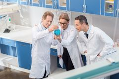 Chemists examining reagent. Team of chemists in lab coats examining a big flask with blue reagent Stock Photo