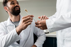 Chemists in lab coats holding test tube with reagent together. Cropped shot of chemists in lab coats holding test tube with reagent together Stock Image