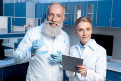 Chemists in lab coats looking at camera and holding flask and digital tablet. Smiling chemists in lab coats looking at camera and holding flask and digital royalty free stock photo