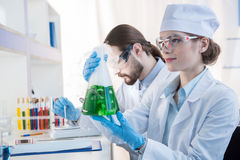 Chemists making experiment. Young professional chemists making experiment with reagent in flask stock photo