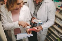 Chemists with a prescription looking for right medicne. Female chemist with prescription pointing at medicine box in male coworker hand in drug store. Chemists royalty free stock photography