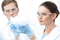 Chemists in protective glasses making experiment with liquid nitrogen Stock Images