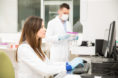 Chemists running some tests in a lab. Couple of good looking chemists running some tests and analyzing blood in a laboratory Royalty Free Stock Photography