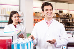 Chemists shop. Man and women pharmacists at the chemists shop royalty free stock photography