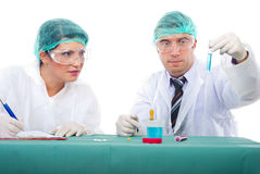 Chemists teamwork analyze tube with liquid. Chemist man holding tube with blue liquid and student woman taking notes in a laboratory,isolated on white background Royalty Free Stock Photography