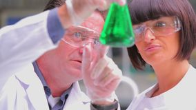 Chemists viewing green liquid. Chemists viewing  green liquid in beaker in the laboratory stock footage