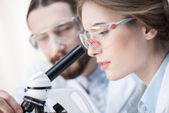 Chemists working with microscope Royalty Free Stock Photo