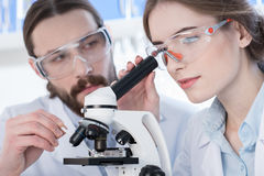 Chemists working with microscope Royalty Free Stock Photos
