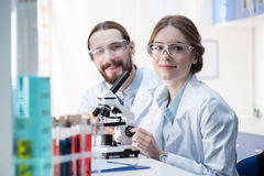 Chemists working with microscope Stock Photography