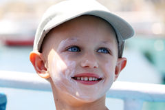 Chemo child. A child with cancer and hair loss pastes herself with sunblock Royalty Free Stock Photo