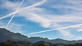 Chemtrails über Bergen Stockfotos