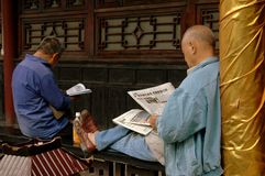 Chengdu, China: Men Reading Newspapers. Two men sitting on a ledge reading Chinese newspapers at the historic Da Ci Temple in Chengdu, China stock photos