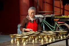 Chengdu, China: Woman Cleaning Candle Holders Royalty Free Stock Photo