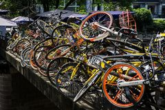 Dockless rental bikes piled on a walkway. Chengdu, Sichuan, China - April 26, 2018: Dockless rental bikes stacked up along the railing of a walking bridge royalty free stock images