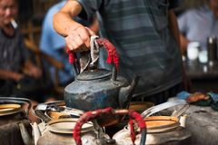 Man holding an old kettle in a chinese ancient tearoom. Chengdu, Sichuan Province, China - Sep 12, 2016: Man holding an old kettle in a chinese ancient tearoom Royalty Free Stock Images