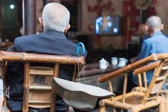 Senior chinese people watching TV in an old tearoom. Chengdu, Sichuan province, China - Sept 12, 2016 : Senior chinese people watching TV in an old tearoom Royalty Free Stock Photos