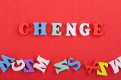 CHENGE-Wort auf dem roten Hintergrund verfasst von den hölzernen Buchstaben des bunten ABC-Alphabetblockes, Kopienraum für Anzeig Stockfoto