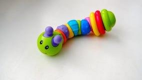 Chenille colorée par jouet sur un fond clair Images stock