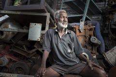 CHENNAI, INDIA - 24 LUGLIO 2017: Una seduta dell'uomo anziano e un vecchio motore Fotografie Stock Libere da Diritti