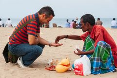A tourist buys coral pearls from a local seller at the popular M stock image