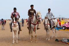 CHENNAI, TAMIL NADU, INDIA - APRIL 28: Drie mensen die op horseback langs de strandboulevard berijden april 28, 2014 in Chennai,  Royalty-vrije Stock Afbeelding