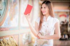 Cheongsam китайского платья женщины традиционные и конверт красного цвета владением Стоковые Изображения RF