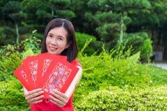 Cheongsam Aziatische vrouw met rode in hand enveloppen, Gong xi fatt cai Stock Foto